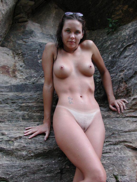 Привлекательная мокрощелка позирует с голыми сиськами у камней