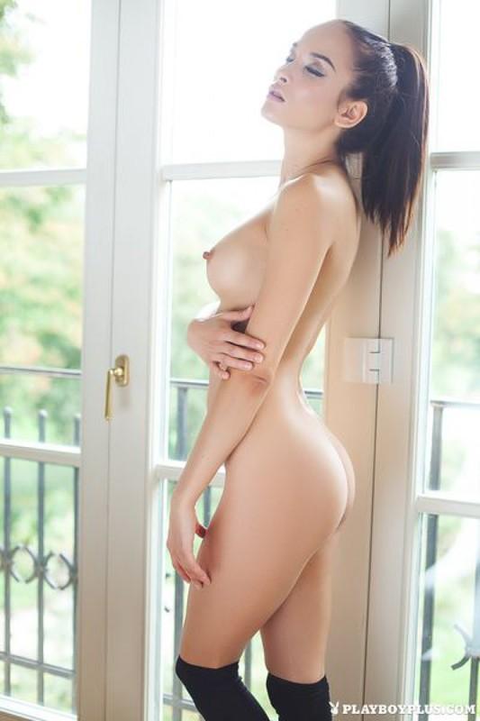 Жасмин страстно двигается в обнаженном виде возле деревянной кушетки