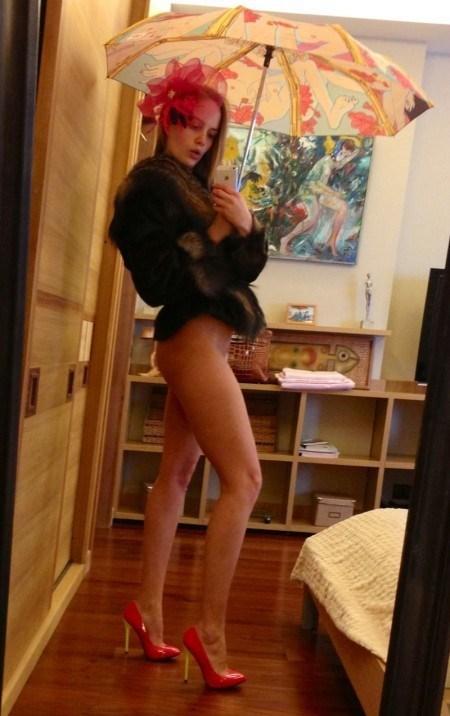 Леди стоит перед зеркалом в соблазнительном наряде