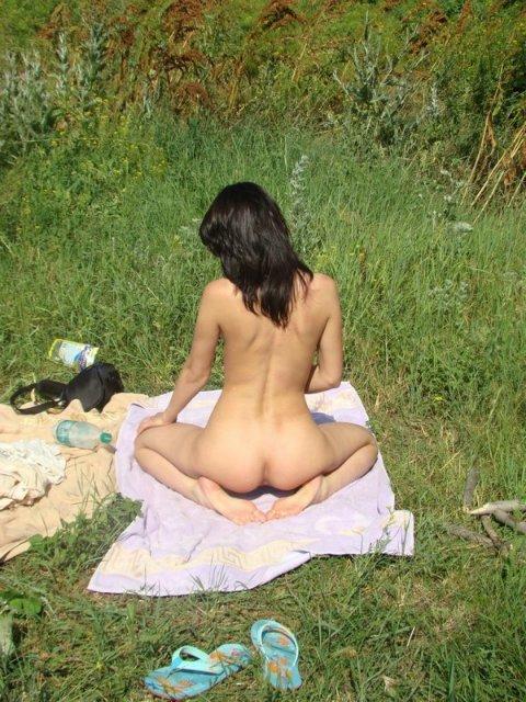 Брюнетка сидит без трусов на пикнике на берегу моря