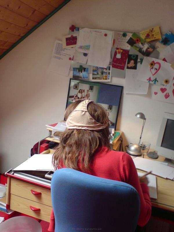 Барышня сидит за столом с собственными трусиками на голове