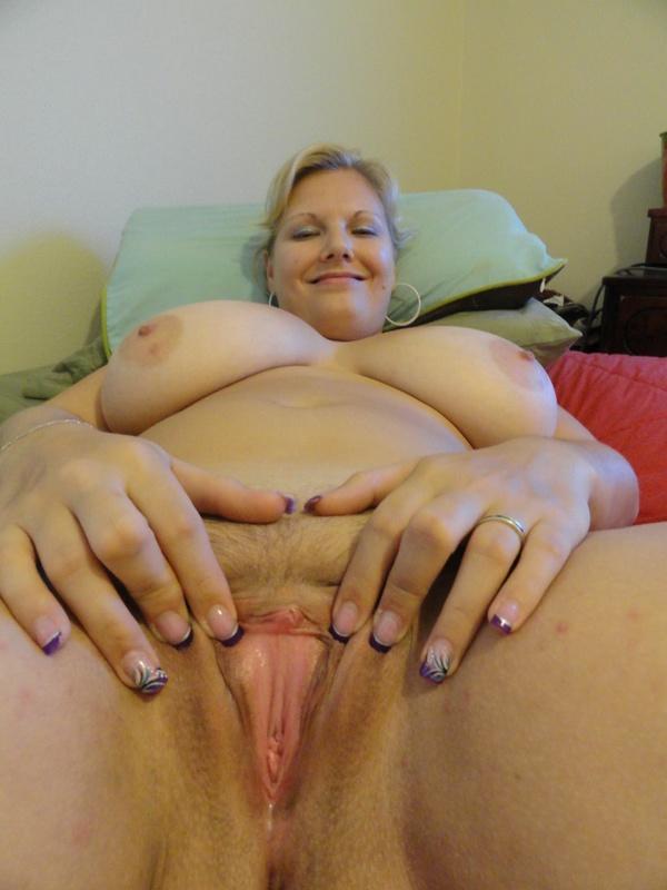 Зрелая баба с большими грудями фотографируется на постели