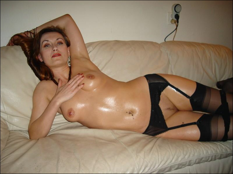 Наполовину раздетая мадам намазалась маслом на белоснежном диване