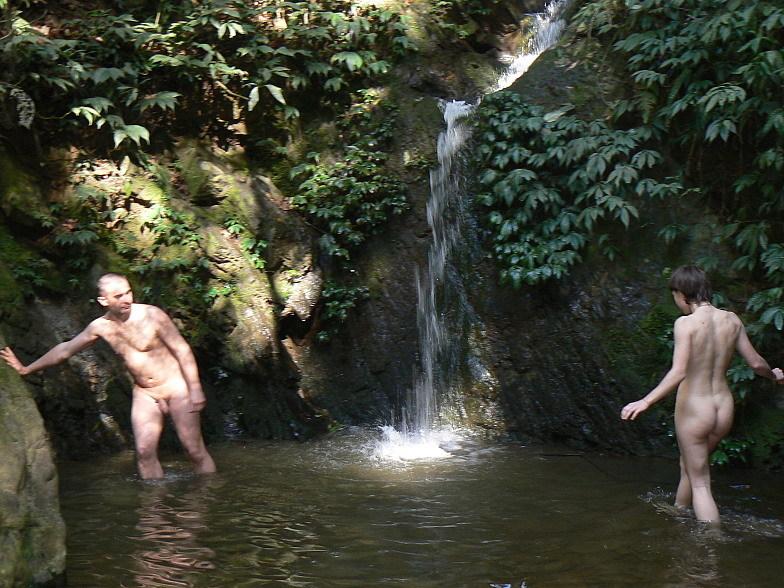 Обнаженная туристка стоит под холодным водопадом