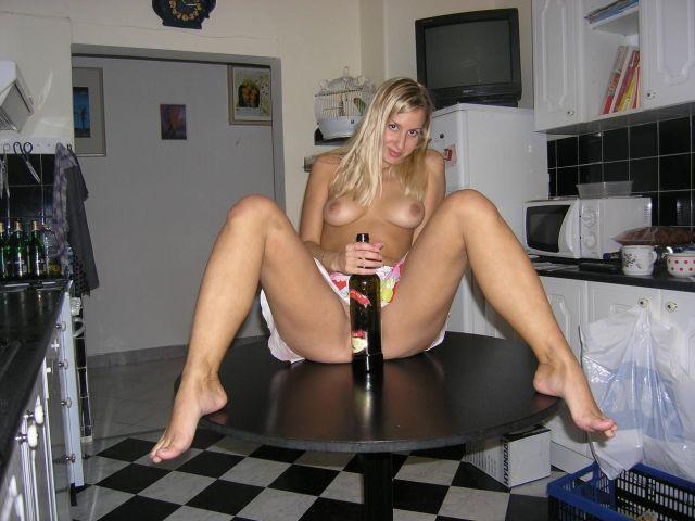 Блистательная модель со свелыми волосами на столике дразнит свою пилотку бутылкой вина