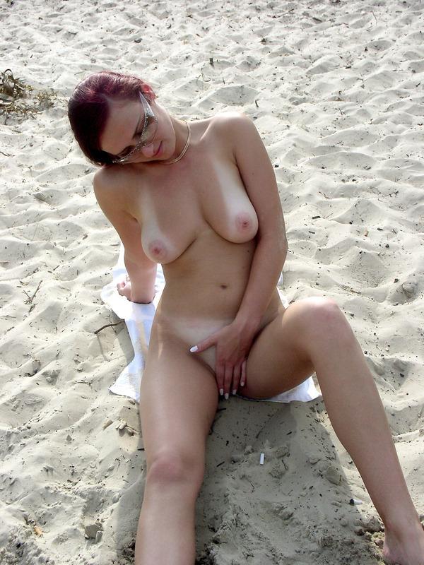 Игривая мамаша на песке массирует пальцами киску