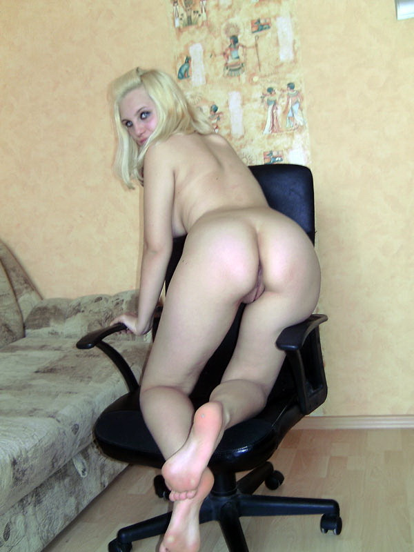 Голая блондинка Аня сидит в черном кресле