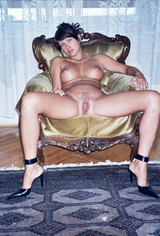 Сидя на раритетной мебели брюнетка светит прелестями