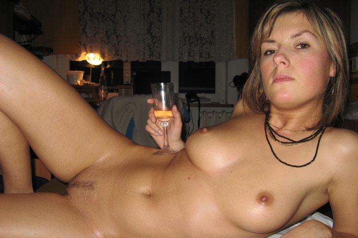 Голая кокетка пьет вино в спальне