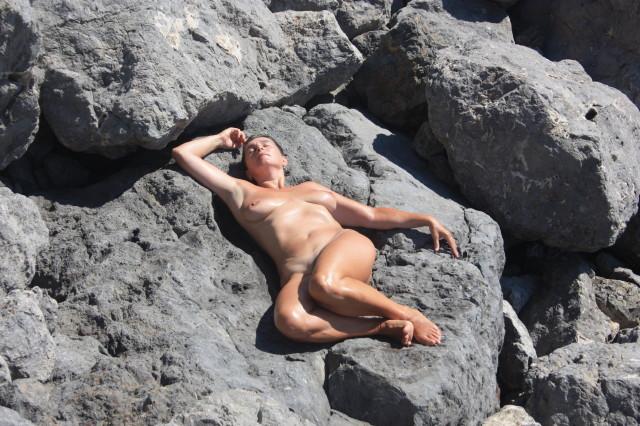 Голая зрелка лежит на камнях возле моря