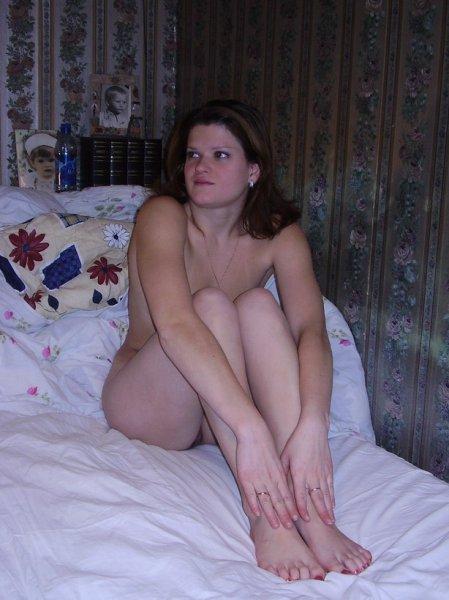 Голая телка сидит на постели