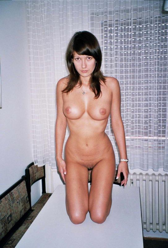 Сексуальная брюнеточка позирует на столе