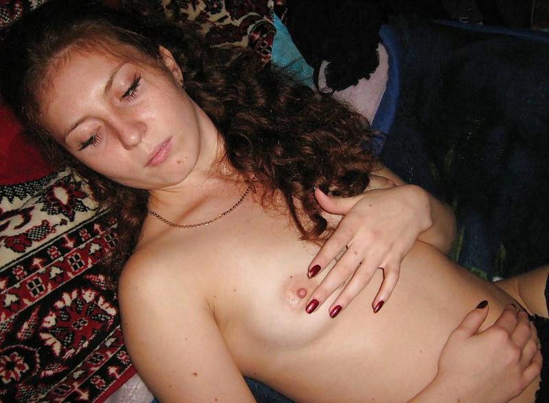 Кудрявая красоточка фотографируется в сетчатых чулочках в постели