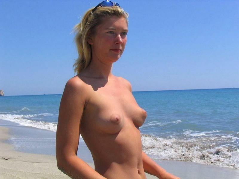 Нудистка загорает на песчаном пляже