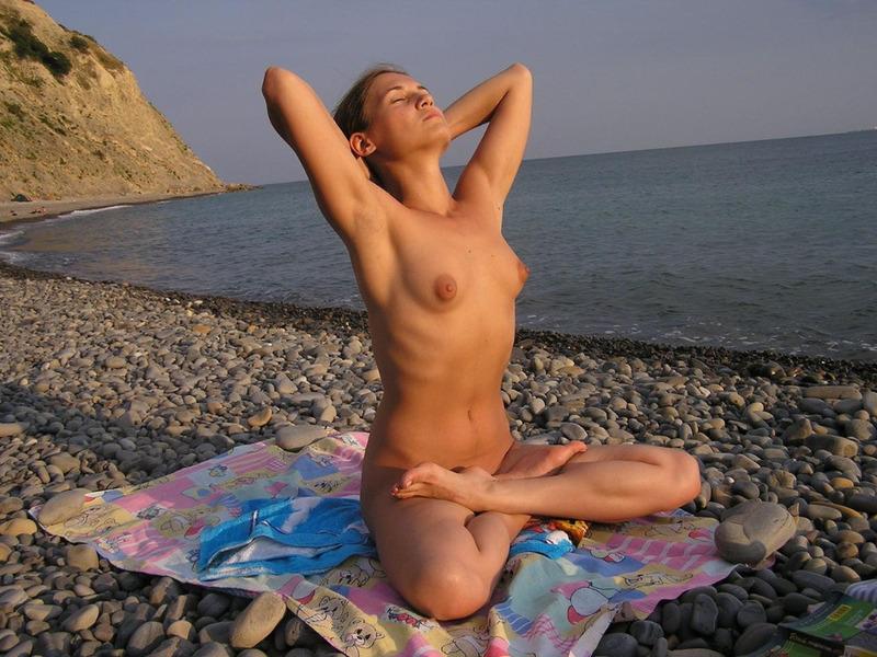 Голая барышня занимается йогой на морском берегу