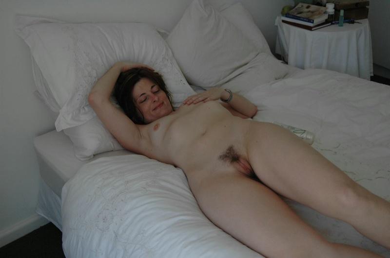 Нескромная милфа без трусиков лежит на кроватке