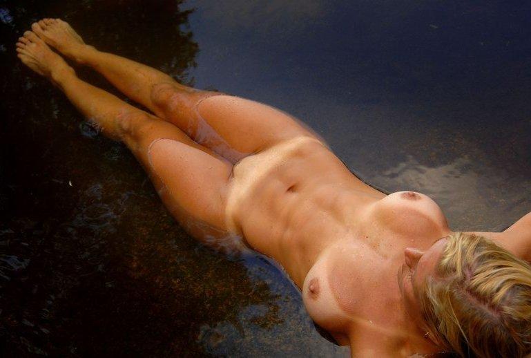 Взрослая гимнастка купается голышом в пруду