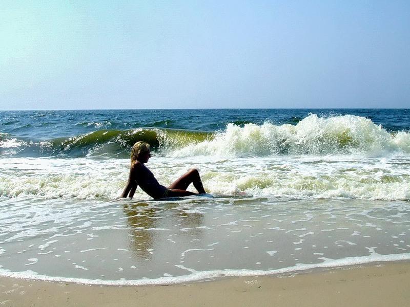 У моря светловолосая девушка делает селфи с голыми дойками