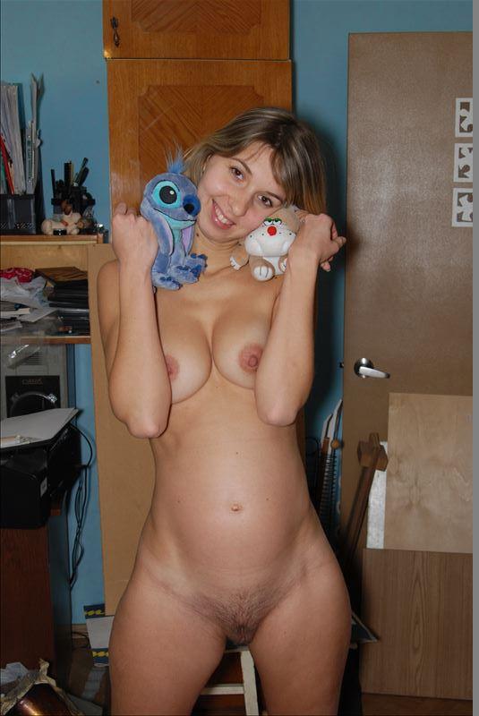 Беременная сучка позирует в спальне без нижнего белья
