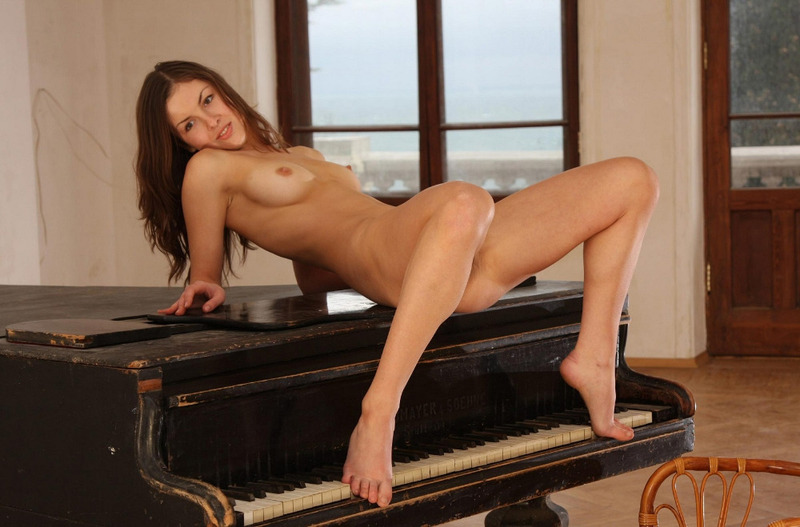 Красивая Александра залезла на черный рояль