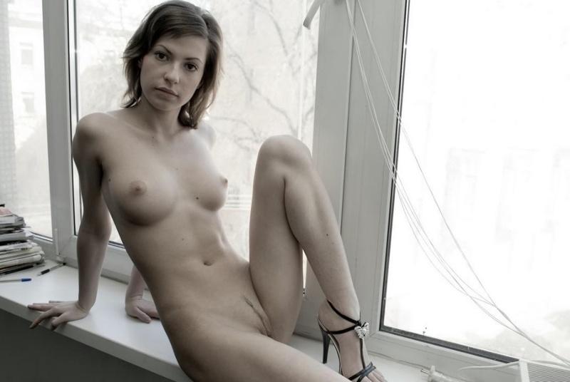 Раздетая красавица устроилась перед окном на подоконнике