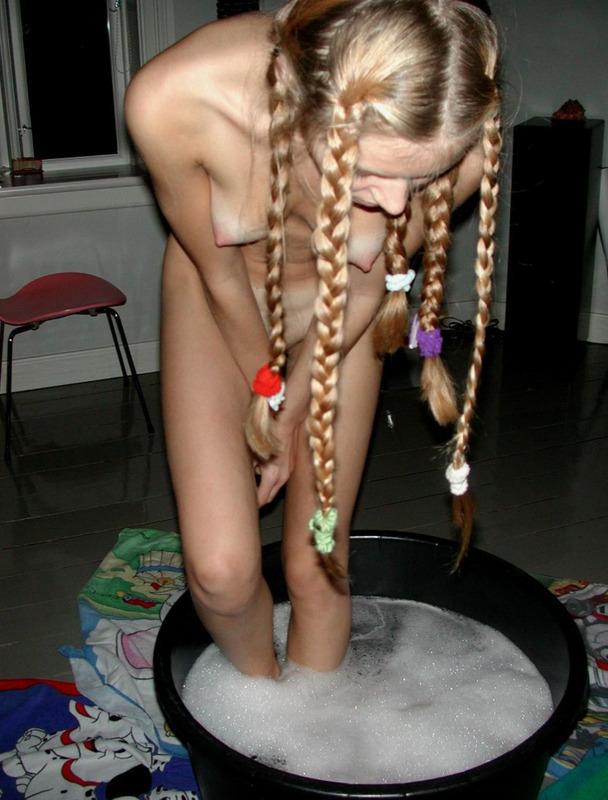 Девчонка с косичками купается в тазике