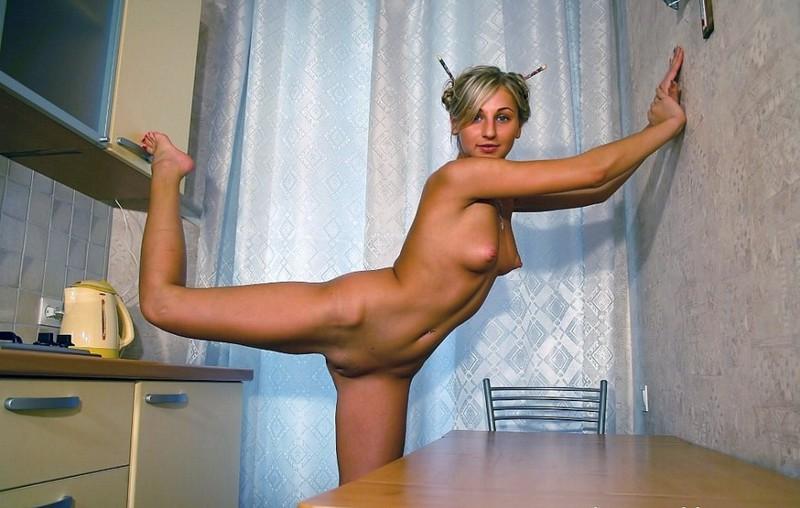 Нагая юная студентка делает гимнастику на столе