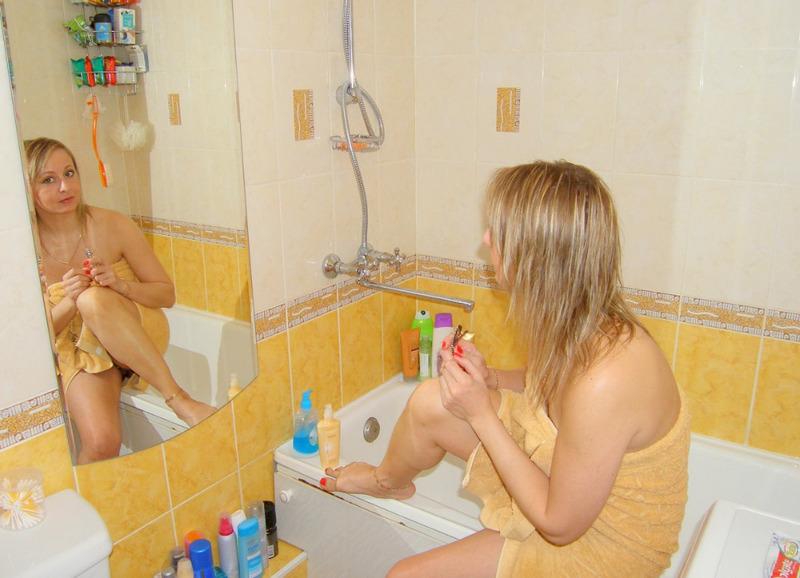 Зрелая блондинка укутывается в полотенце после водных процедур