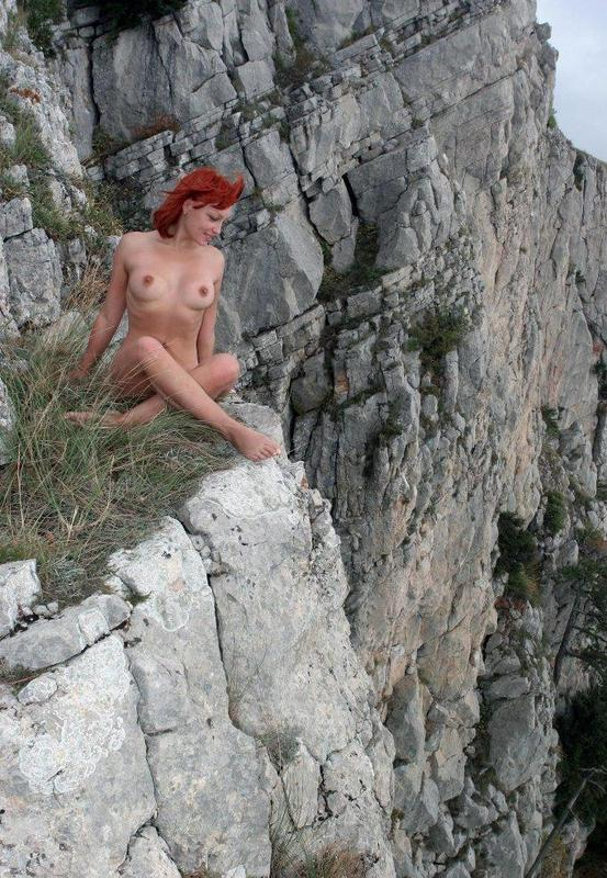 Рыженькая бестия хвастается грудями на скале
