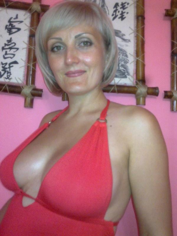 Блондинистая мамка позирует на фоне розовой стены без лифа