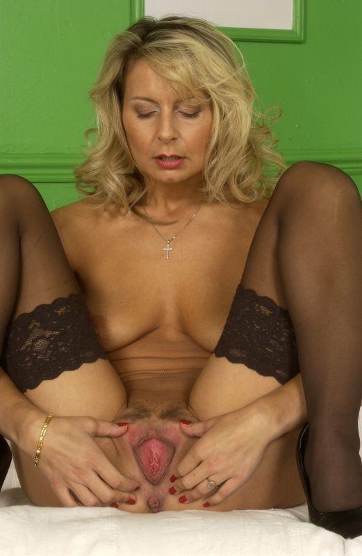 Взрослая модель со свелыми волосами на диванчике хвастается розовой писькой