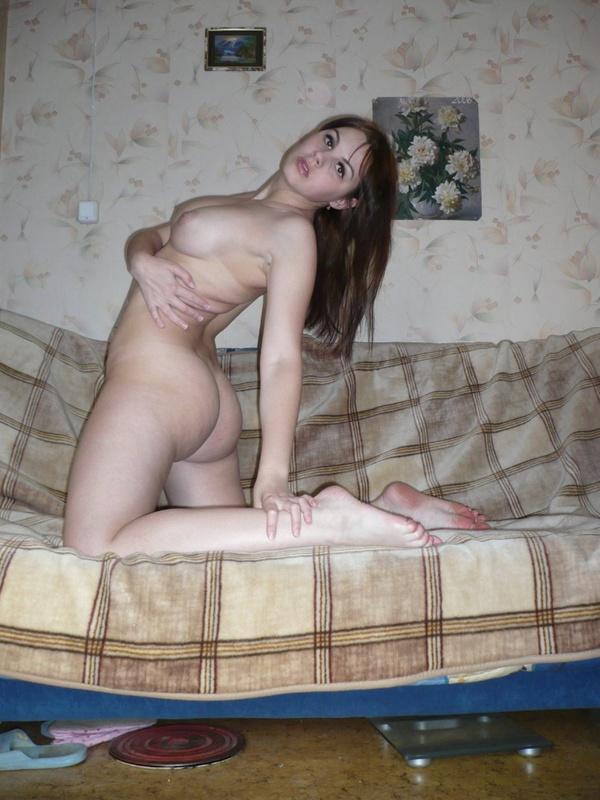 Аппетитная брюнетка с голыми сиськами стоит в чулках