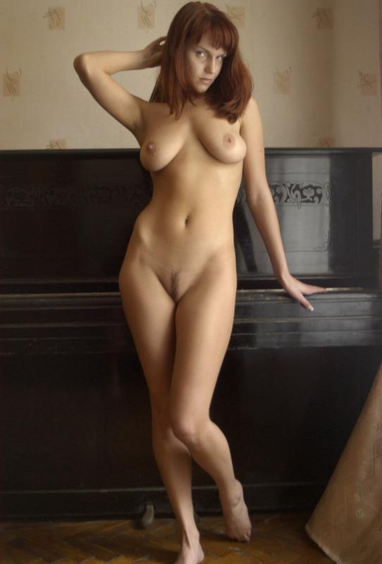 Рыжеволосая маромойка светит большими титьками у рояля