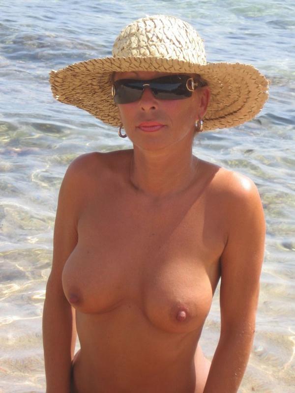Загорелая тетка отдыхает на берегу моря в обнаженном виде