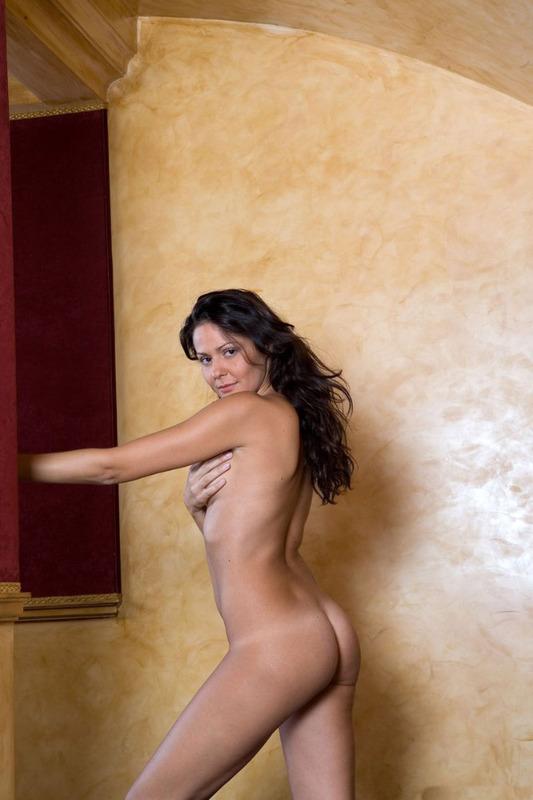 Голая брюнетка позирует голая в роскошных апартаментах