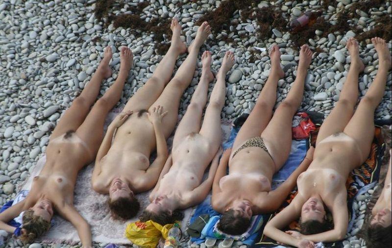 Раздетые тёлки лежат на галечном песке