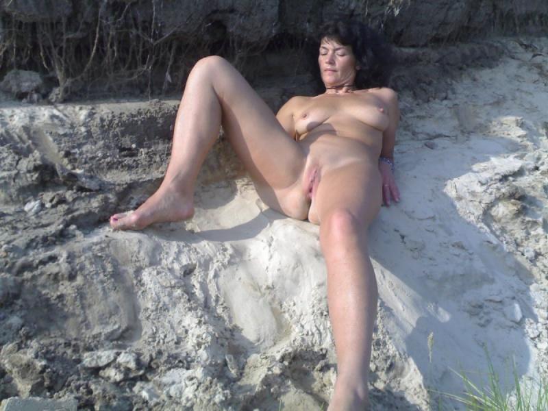 Зрелая на открытом воздухе присела на песок обнаженной попой