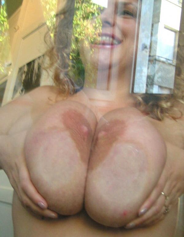 Кудрявая сучка кладет большие буфера на стекло