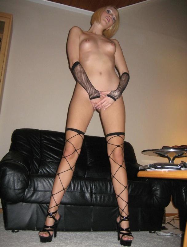 Блондинка на кожаном диване валяется в чулках