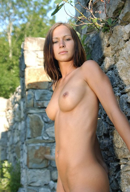 Обнаженная принцесса стоит около каменной стены секс фото
