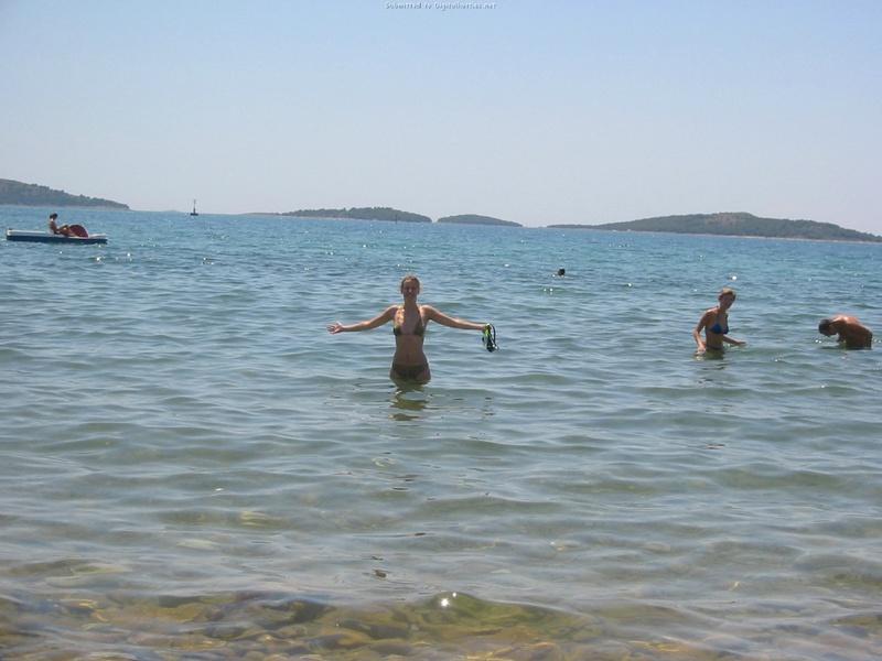 Бикса стоит у моря и демонстрирует дойки