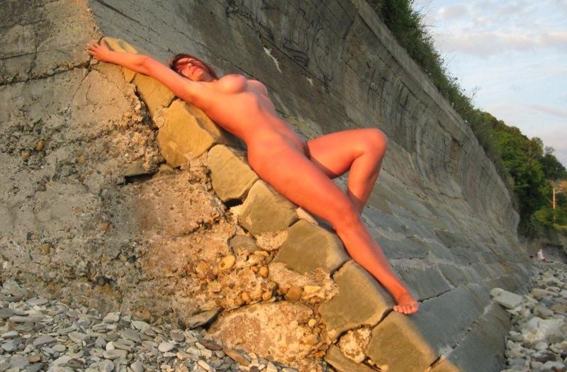 Зрелая нимфа с огромными титьками гуляет голышом по берегу моря