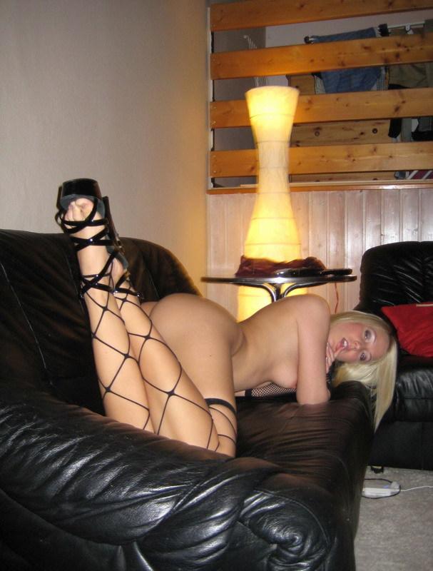 Лежа на черном диване, нимфа задирает ноги показывая сочную писю