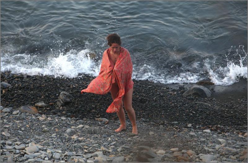 Голая нудистка выходит на берег из воды