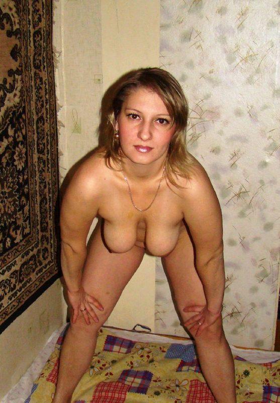 Женщина показывает влагалище возле настенного ковра