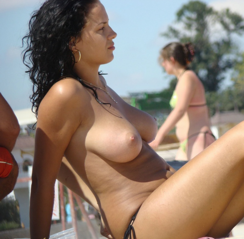 Брюнетка загорает топлес на пляже