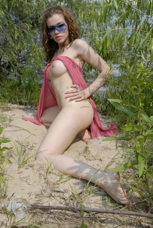 На берегу водоема девка разделась в кустах