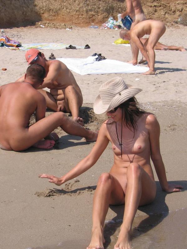 Спортивная красотка делает селфи на нудистском песке
