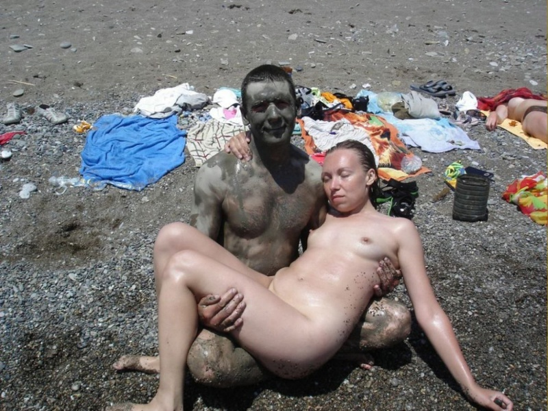 Группа путешествующих нудистов делает грязевые маски на пляже