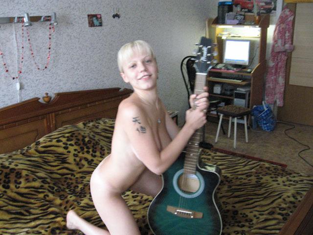 Голая музыкантка делает селфи в кровати с гитарой в руках